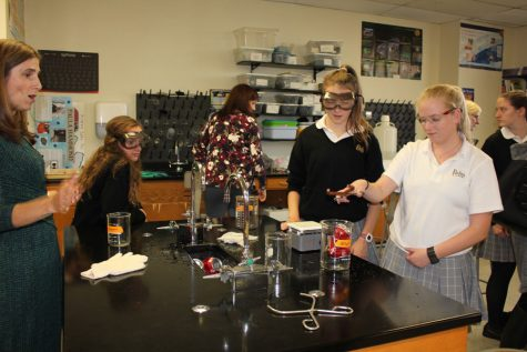 Katherine Halley '19 and Anne Fraser-Jones '19, perform a Chemistry experiment in front of guest