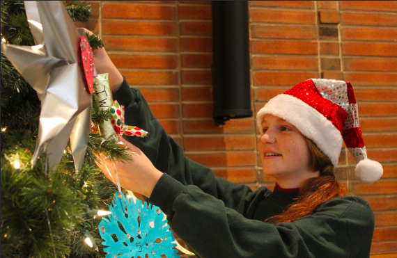 Representatives from each homeroom hang ornaments for their class