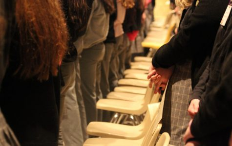 Students stand in prayer.