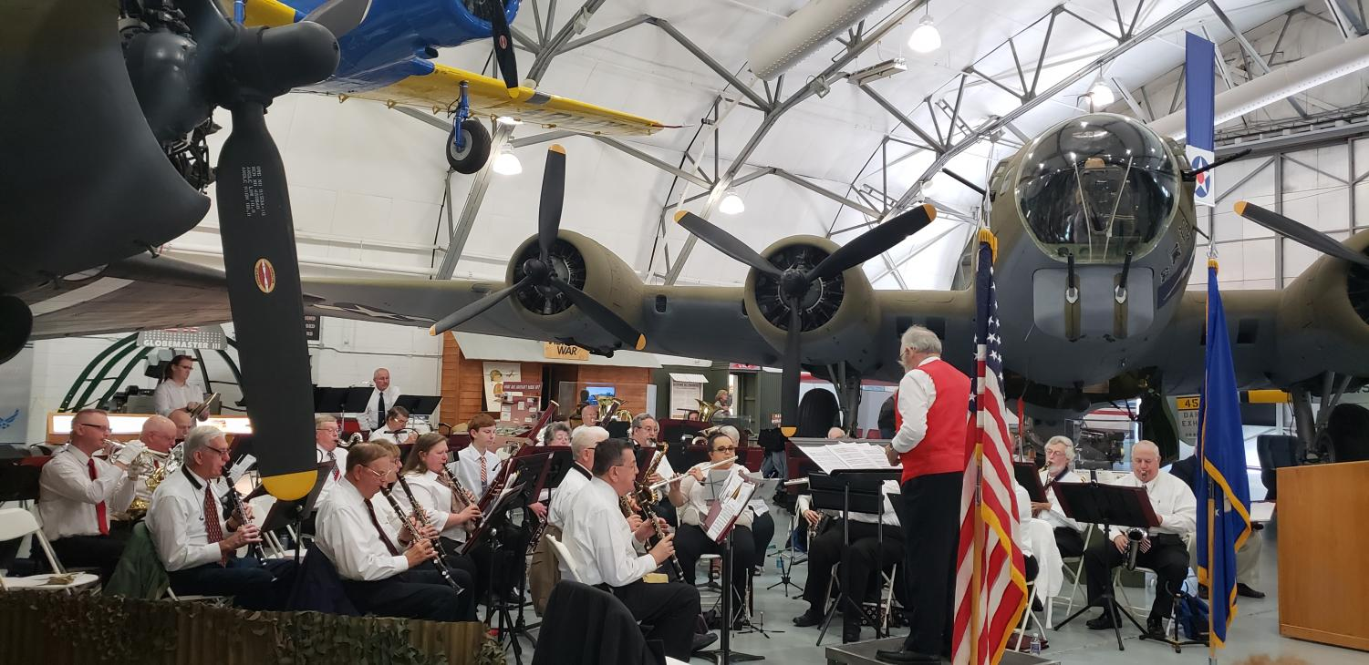 The Milford Community Band performs during the ceremony in the AMC Museum's hangar. Two restored aircraft from World War II, a C-47 cargo lifter and a B-17 bomber, served as the backdrop for the day's events.