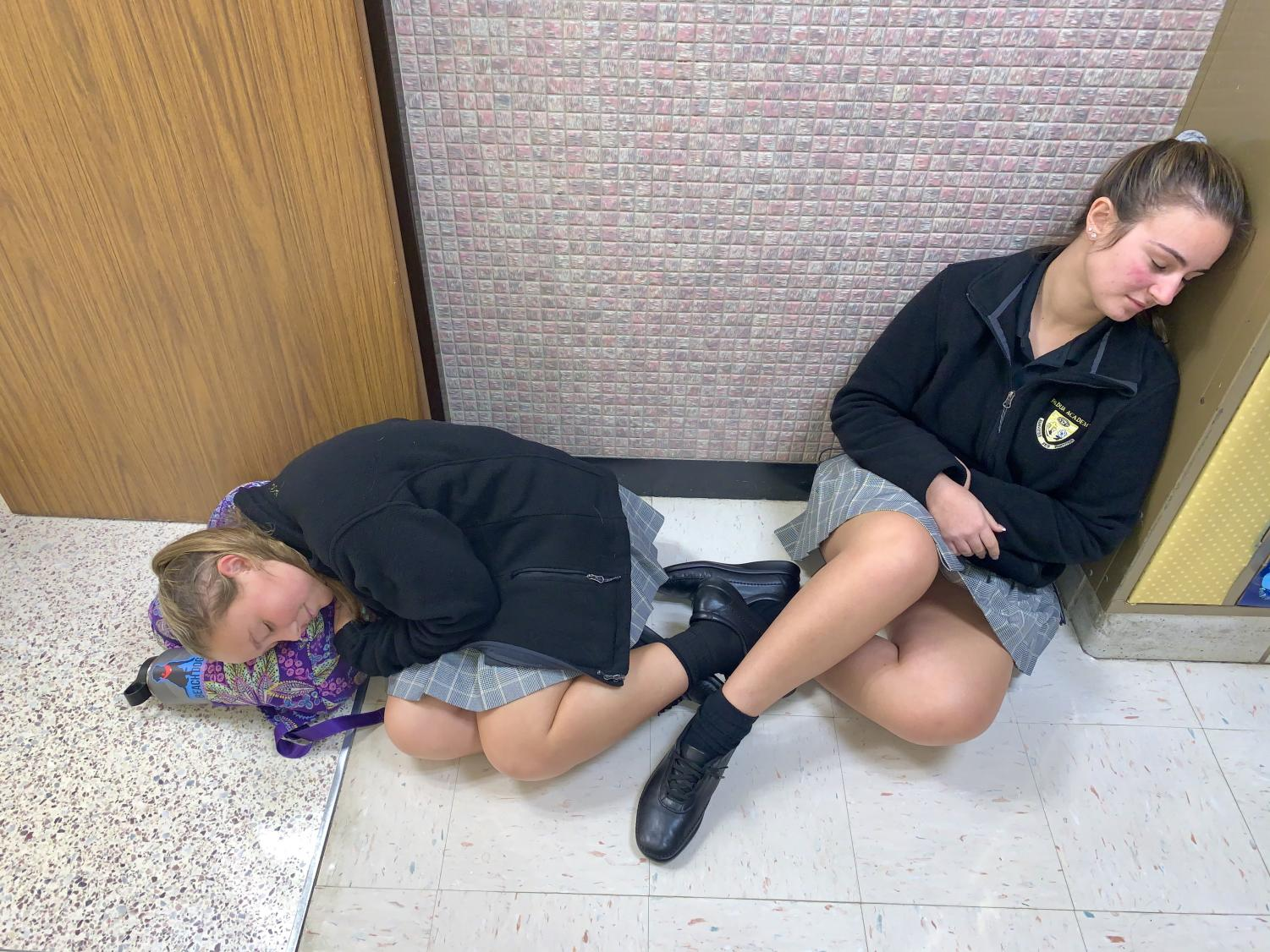 Two students asleep during class because they didn't receive enough sleep the night before.
