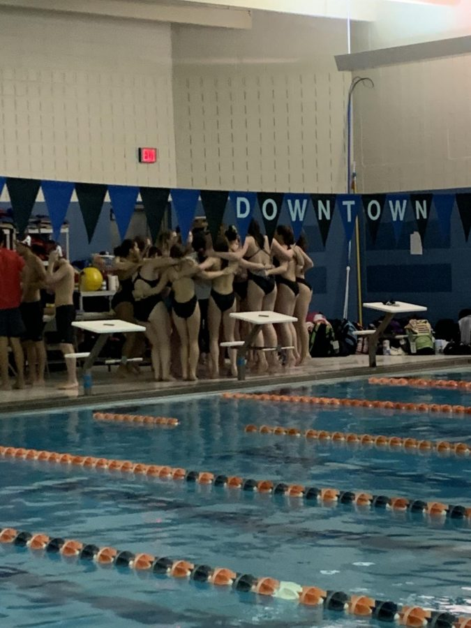 The+members+of+the+swim+team+being+lead+in+a+cheer+before+the+first+event+to+get+them+excited+for+the+meet.