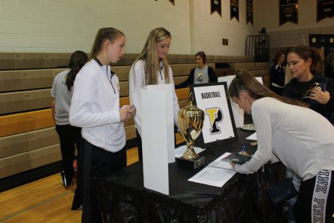 Visitor signs up at the basketball information desk