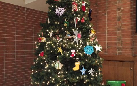 A picture of the beautiful finished Christmas tree. It contains many unique ornaments created by homeroom representatives. There are also a variety of different presents under the tree.