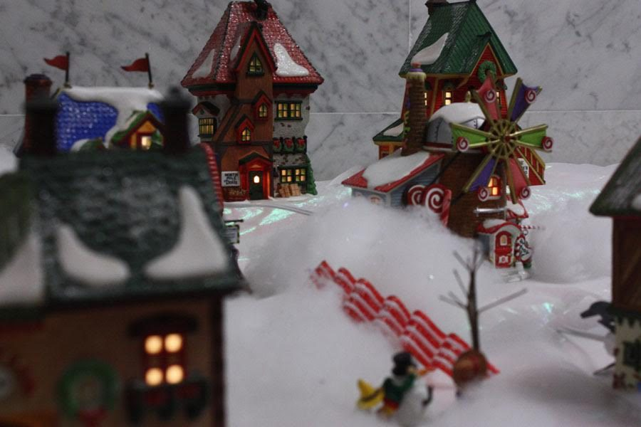 This+is+a+picture+of+another+piece+of+the+train+set.+In+the+picture%2C+tiny+decorated+houses+are+depicted.+These+houses+also+contain+many+different+Christmas+colors+