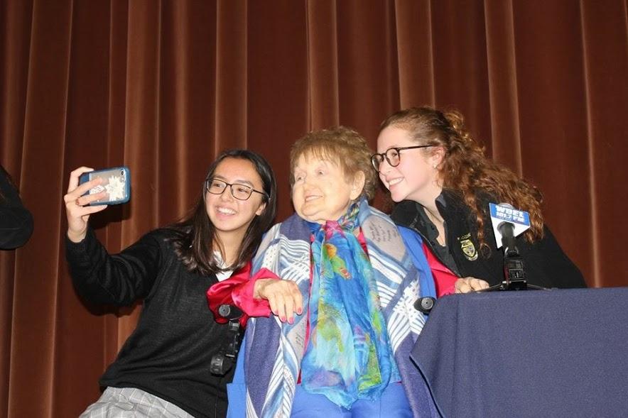 Seniors Lauren Mottel and Sarah Jane Mee take a picture with Auschwitz survivor Eva Kor.
