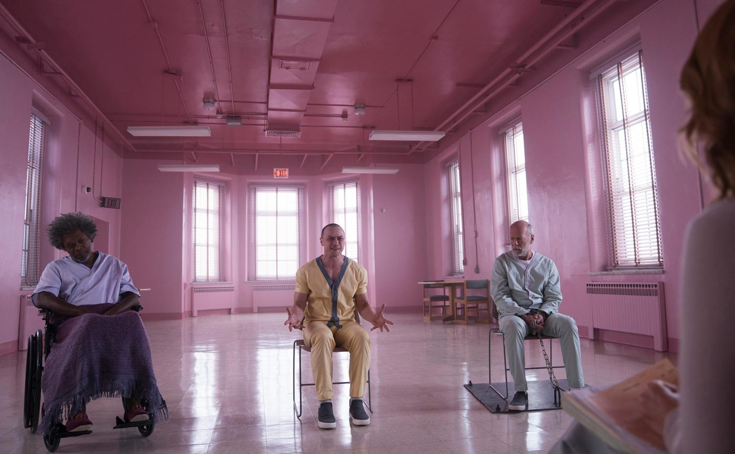 Elijah Prince (Samuel L. Jackson), Kevin Wendell Crumb (James McAvoy), and David Dunn (Bruce Willis) sit in a room while they are interrogated.