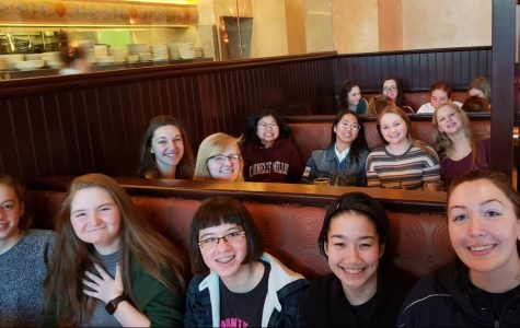 Team members smile during their celebratory dinner at the Cheesecake Factory.