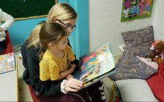 Freshman Caitlin Suter reads a book to her new friend at Mom's House.