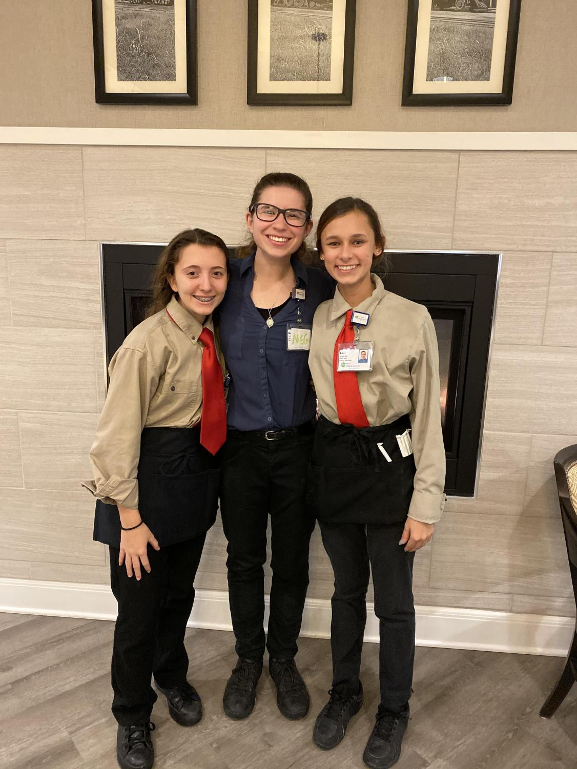 """Marissa Manzi (left) stands with two co-workers at her job. Since beginning her job, Manzi feels proud of her newfound income because, """"I earned it. I worked hard for it."""