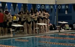 The members of the swim team being lead in a cheer before the first event to get them excited for the meet.