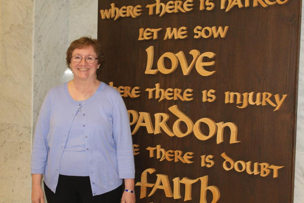 """Dr. McClory poses in front of the prayer wall in the lobby. McClory said that her favorite part of her job is working with the staff. """"It's really a pleasure to work with other people in our building- other adults that care about passionately about our school and our students,"""" she said."""