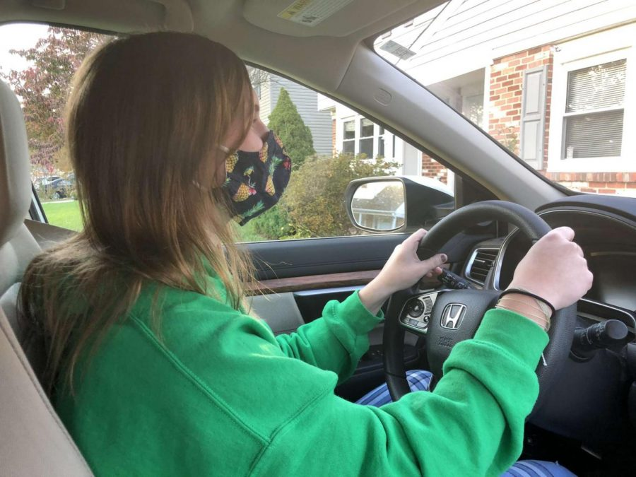 Kacey Dove driving to her house with a mask on.