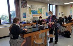 Mrs. Fundakowski hands out a test to her Honors Chemistry students. After an unexpected resignation, she and Dr. McClory stepped up to teach two chemistry sections each.
