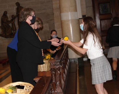 A freshman receives a yellow rose bud from Dr. McClory at Freshman Convocation. Students and families gathered to celebrate the beginning of their high school journey.