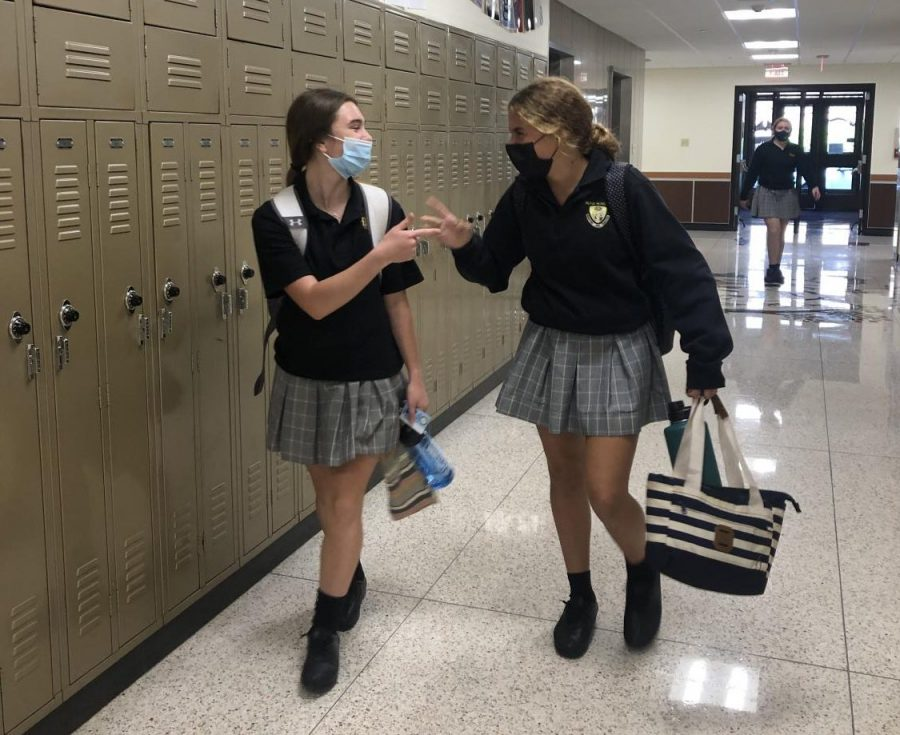 Sophomores Kelsey Wolff and Reese Flanagan share a laugh on the way to their next class.